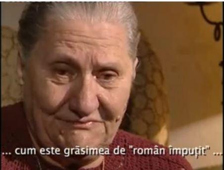 """Purtătoarea pandantivului pe care scrie NU UITA!, supraviețuitoare a genocidului din Ip, a fost martoră când trupul mamei ei a fost spintecat în două, cu baioneta, pentru că un sălbatic hortyst, înainte să-i arunce trupul în groapa comună, a fost curios să vadă cum arată """"grăsimea de român împuțit"""". Cum să uite această femeie atrocitățile comise de unguri în Transilvania asupra românilor și a evreilor trimiși în lagărele de exterminare?! (imagine din filmul """"NU UITA!"""")"""
